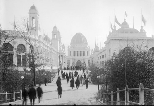 At the Chicago World's Columbian Exposition, visitors walk along a pathway between several of the fair buildings towards a domed building. Photo Smithsonian Institution Archives.