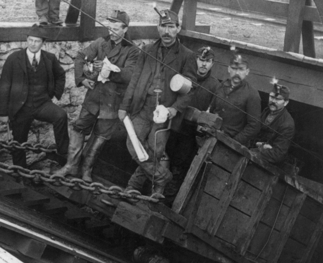 Miners Going into the Slope, Hazelton, Pa. / 5 miners in railroad car about to descend into coal mine. Circa 1905