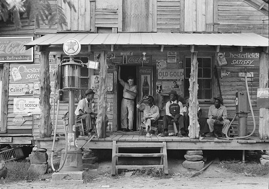 PHOTO: Country store on dirt road. Sunday afternoon, July 1939. Note the kerosene pump on the right and the gasoline pump on the left. Rough, unfinished timber posts have been used as supports for porch roof. Gordonton, North Carolina. Farm Security Administration - Office of War Information Photograph Collection (Library of Congress)